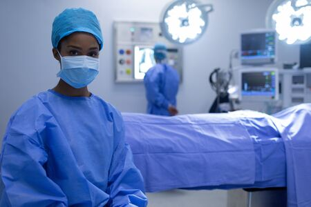 Front view of Mixed-race female surgeon sitting with surgical mask in operation theater at hospital