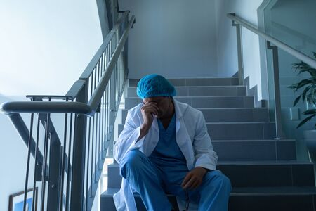 Front view of tensed Caucasian male surgeon with hand on forehead sitting on stairs at hospital