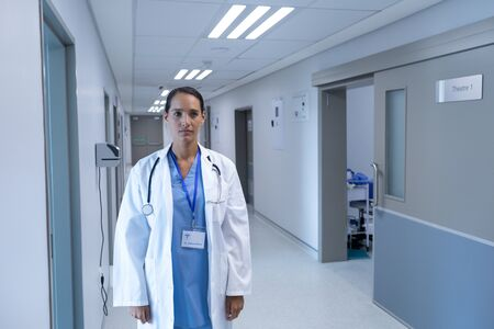 Front view of Caucasian female doctor standing in the corridor at hospital Stok Fotoğraf