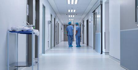 Vista trasera de diversos cirujanos hablando entre sí en el pasillo del hospital