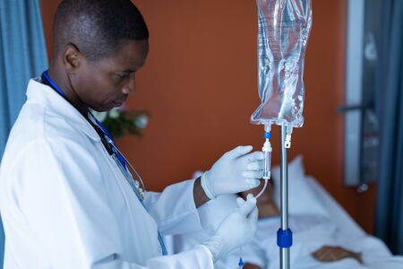 Side view of African-american male doctor injecting injection to female patients intravenous drip in the ward at hospital Stock Photo