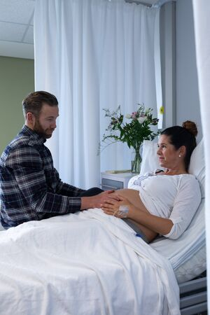 Side view of Caucasian man comforting pregnant woman in ward at hospital