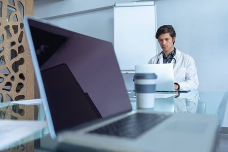 Front view of male Caucasian doctor using laptop at table in conference room of hospital