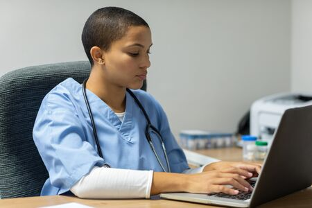 Front view of mixed-race female doctor working on laptop at desk of examination room in hospital