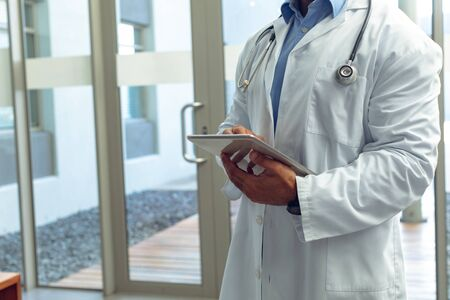 Mid section of Mixed-race male doctor using digital tablet in lobby at hospital