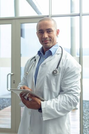 Front view of Mixed-race male doctor looking at camera while using digital tablet in lobby at hospital Imagens