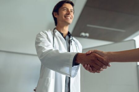 Low angle view of Caucasian male doctor shaking hand with female Caucasian nurse in the hospital Imagens