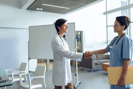 Zijaanzicht van mannelijke gelukkige blanke arts die handen schudt met lachende vrouwelijke blanke verpleegster in het ziekenhuis
