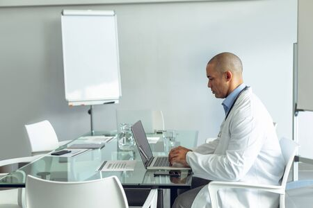 Side view of Mixed-race male doctor using laptop at table in the hospital