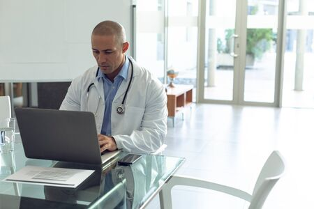 Front view of Mixed-race male doctor using laptop at table in the hospital Stock Photo