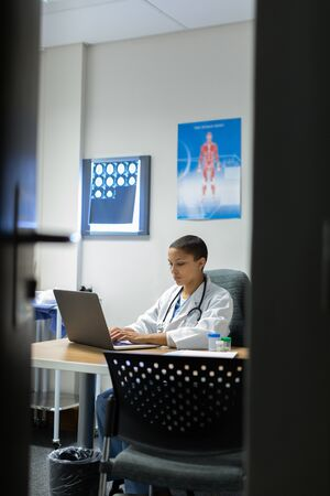 Front view of mixed-race female doctor working on laptop at desk of examination in hospital