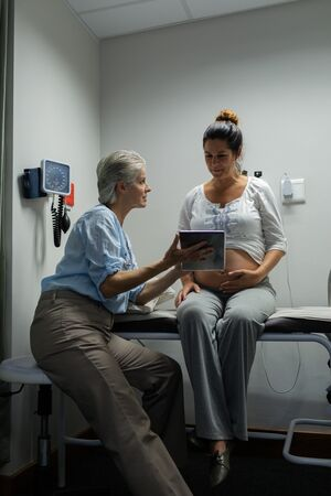 Side view of Caucasian female doctor discussing with pregnant woman over digital tablet in hospital
