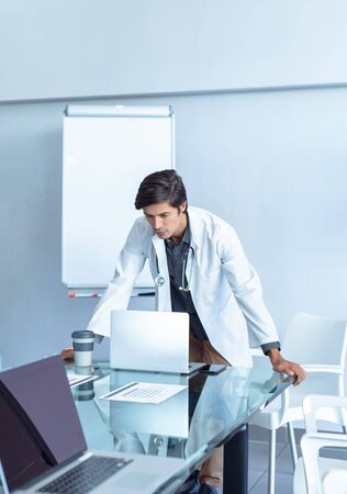 Front view of male Caucasian doctor standing while using laptop at table of conference room in the hospital