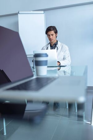 Front view of Caucasian male doctor using laptop at table of conference room in the hospital