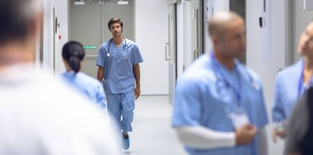 Front view of young Caucasian male surgeon walking in corridor at hospital. In the blurred foreground diverse colleagues are discussing in the hallways.
