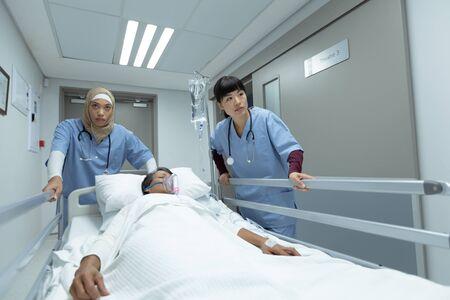 Zijaanzicht van diverse vrouwelijke artsen die een noodbed in de gang in het ziekenhuis duwen. Gemengd ras vrouwelijke patiënt met zuurstofmasker liggend in brancard bed. Stockfoto