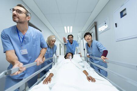 Vista frontal del equipo médico diverso empujando la camilla de emergencia en el pasillo del hospital. Paciente de raza mixta