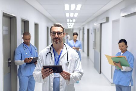 Front view of Caucasian male doctor standing with digital tablet in corridor at hospital. In the background diverse colleagues are working in the hallways