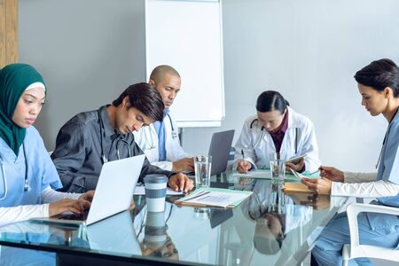 Front view of diverse medical team working together at table in hospital. Coffee cup, glass of water, clipboard, medical folders, and laptop are on the table.