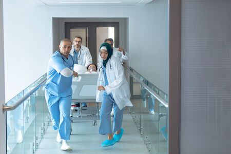 Vista frontal de diversos médicos empujando la camilla de emergencia en el pasillo del hospital. Paciente de sexo femenino asiático está acostado en la cama de la camilla. Foto de archivo