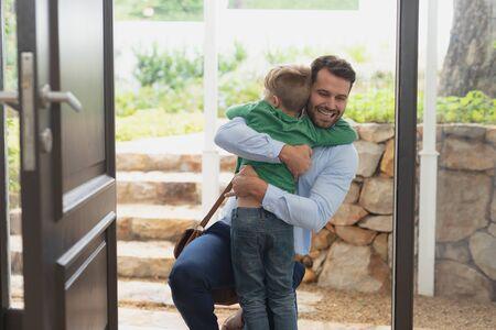 Vorderansicht des glücklichen kaukasischen Vaters, der seinen Sohn umarmt, als er das Haus betritt