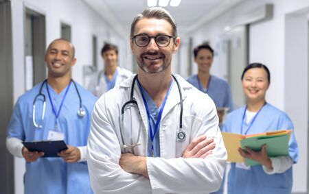 Front view of diverse medical team of doctors looking at camera while holding clipboard and medical files in corridor at hospital. Caucasian male surgeon has his arms crossed.