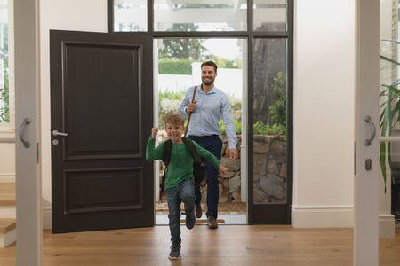Vooraanzicht van blanke vader en zoon die een comfortabel huis binnenkomen