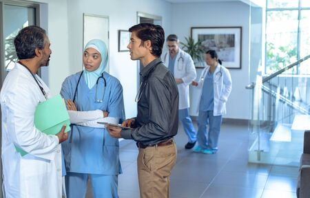 Side view of diverse medical team of doctors talking with each other in lobby at hospital. In the background colleagues are discussing in the hallways.