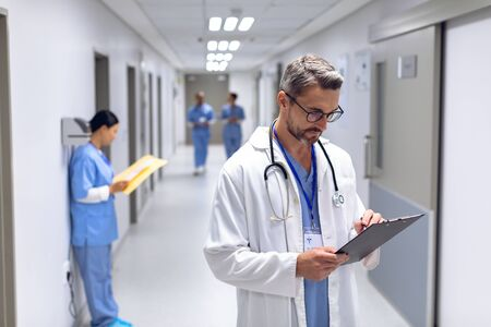 Front view of Caucasian male doctor writing on clipboard in corridor at hospital. In the background diverse colleagues are discussing or making notes in the hallways