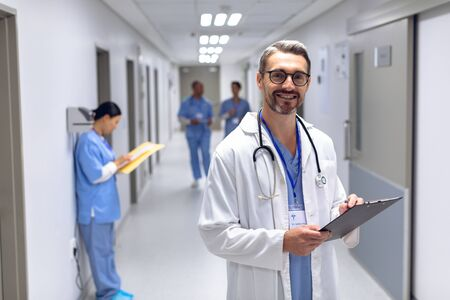 Portrait of Caucasian male doctor looking at camera while writing on clipboard in corridor at hospital. In the background diverse colleagues are discussing in the hallways