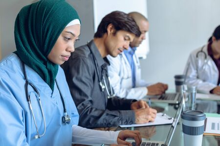 Side view of diverse medical team working together and using laptop and clipboard at table in hospital.