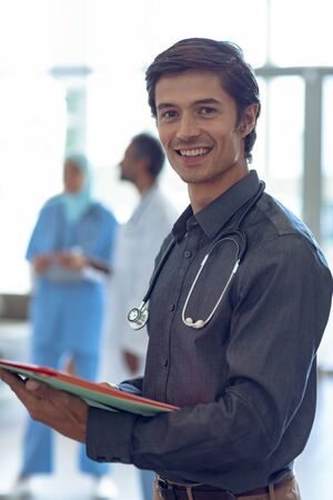 Side view of Caucasian male doctor holding medical file and looking at camera in hospital. In the background diverse colleagues are discussing in the hallways.
