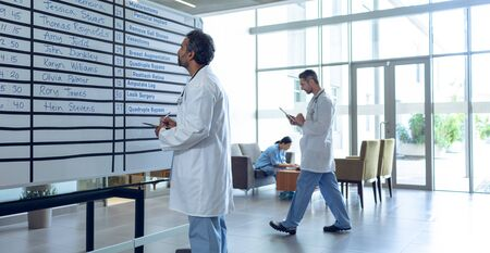 Side view of mixed-race male doctor checking his shifts on chart at hospital. In the background diverse colleagues are working in the hallways.