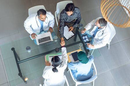 High angle view of diverse medical team working together at table in hospital. Coffee cup, medical folders, clipboard, digital tablet and laptop are on the table. Imagens - 124671520