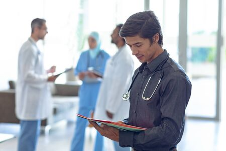 Side view of Caucasian male doctor looking at medical file in hospital. In the background diverse colleagues are discussing in the hallways.