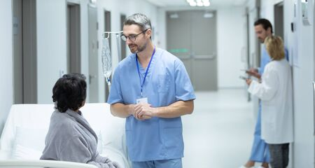 Front view of Caucasian male doctor interacting with disabled female patient in the corridor at hospital Stock Photo