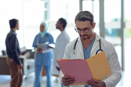 Front view of Caucasian male doctor looking at medical file in hospital. In the background diverse colleagues are discussing in the hallways.