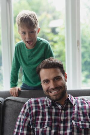 Front view of happy Caucasian father and son looking at camera in a comfortable home