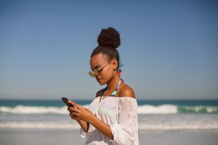 Side view of beautiful African american woman in sunglasses using mobile phone at beach in the sunshine Stock Photo