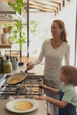 Front view of happy Caucasian mother and son preparing food in kitchen at comfortable home Stock Photo