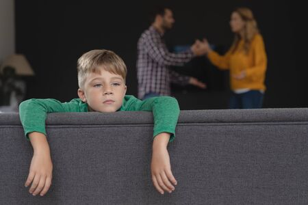 Front view of sad boy leaning on sofa while Caucasian parents arguing in background in a comfortable home Stock Photo