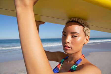 Side view of beautiful African american woman in bikini carrying the surfboard on her head at beach in the sunshine Stock Photo