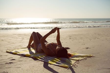 Side view of Caucasian woman using mobile phone while relaxing on picnic blanket at beach in the sunshine