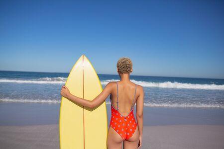 Rückansicht einer afroamerikanischen Frau in Badebekleidung, die mit Surfbrett am Strand in der Sonne steht