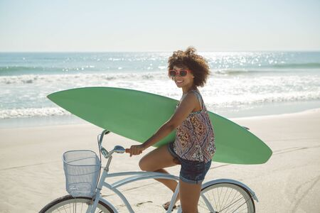 Front view of beautiful African american woman holding a surfboard with bicycle at beach Stockfoto