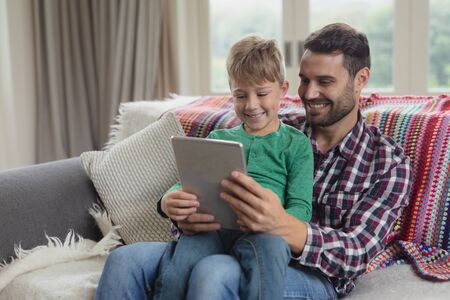Front view of Caucasian father and son using digital tablet on sofa in a comfortable home Imagens