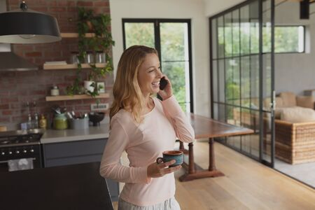 Side view of happy Caucasian woman with coffee cup talking on mobile phone in a comfortable home Stock Photo
