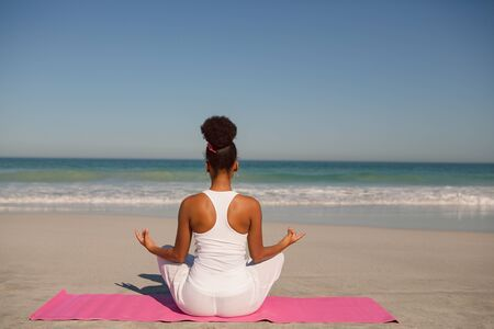 Rear view of African american woman doing yoga on exercise mat at beach in the sunshine