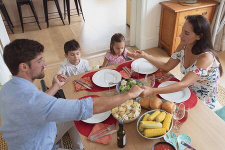 High view of Caucasian family praying together before having lunch at dining table in comfortable home