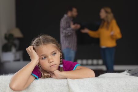 Front view of sad girl leaning on sofa while Caucasian parents arguing in background in a comfortable home Stock Photo